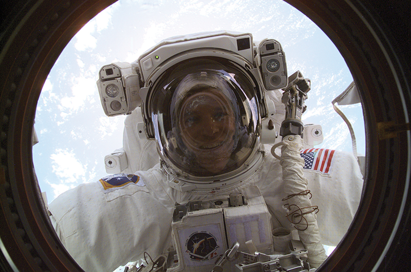 Astronaut Scott Parazynski in a spacesuit looks through a window on the space station with Earth behind him