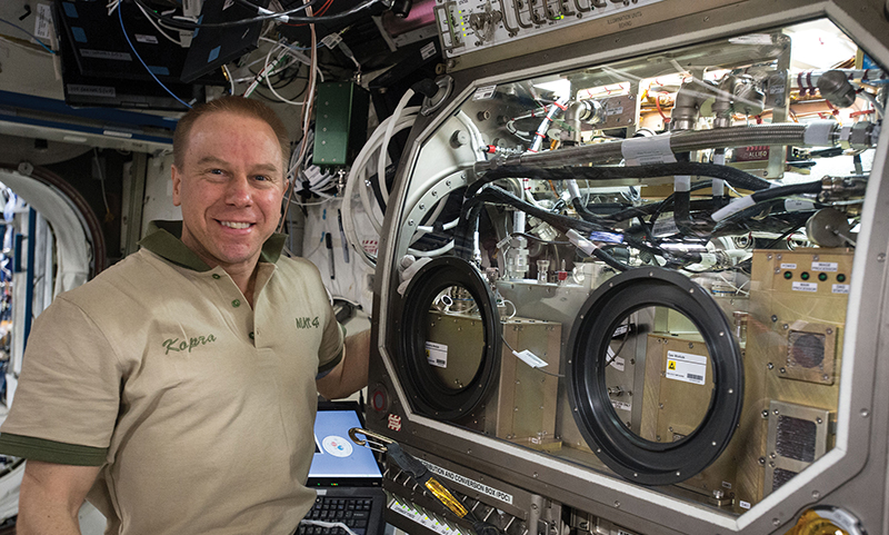 U.S. astronaut Tim Kopra on the space station next to the Packed Bed Reactor Experiment