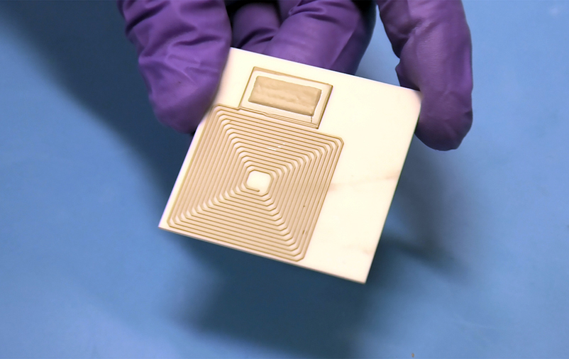 A hand holding a gold-colored ultracapacitor chip
