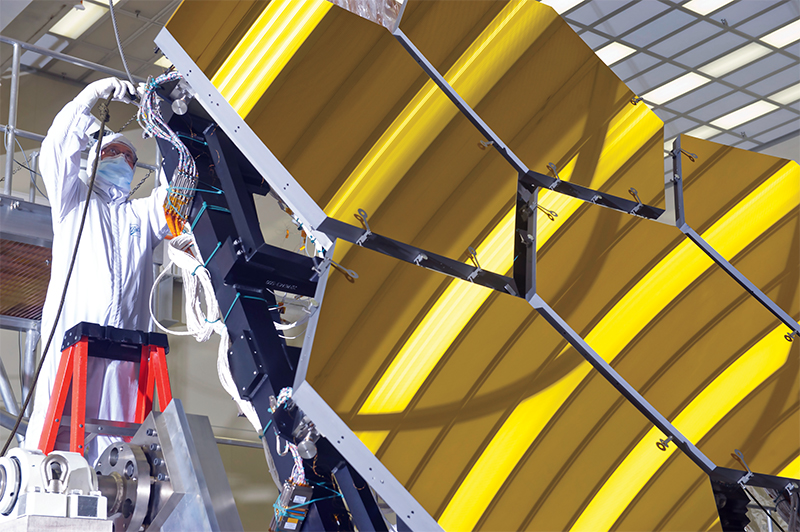 Engineer in clean suit works on the James Webb Space Telescope mirror installation