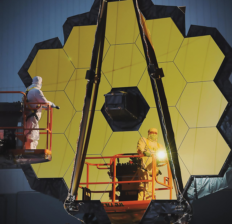 Person in cleansuit shining a flashlight into the gold-plated mirrors of the James Webb Space Telescope