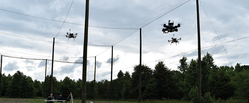 Three small drones fly above a field