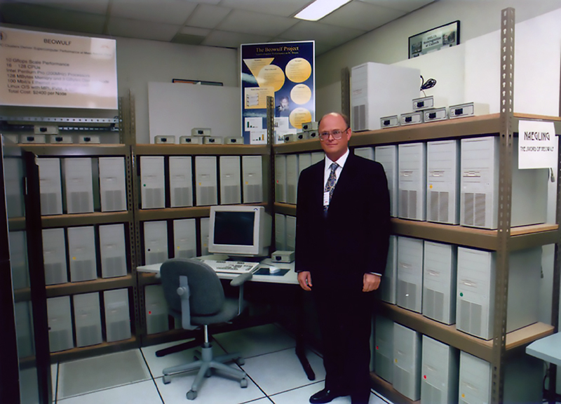 Thomas Sterling stands by a PC on a desk with dozens of CPUs on shelves behind him