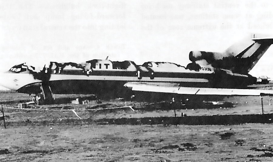 A black and white image of an airliner on the ground with the entire top burned off after a crash