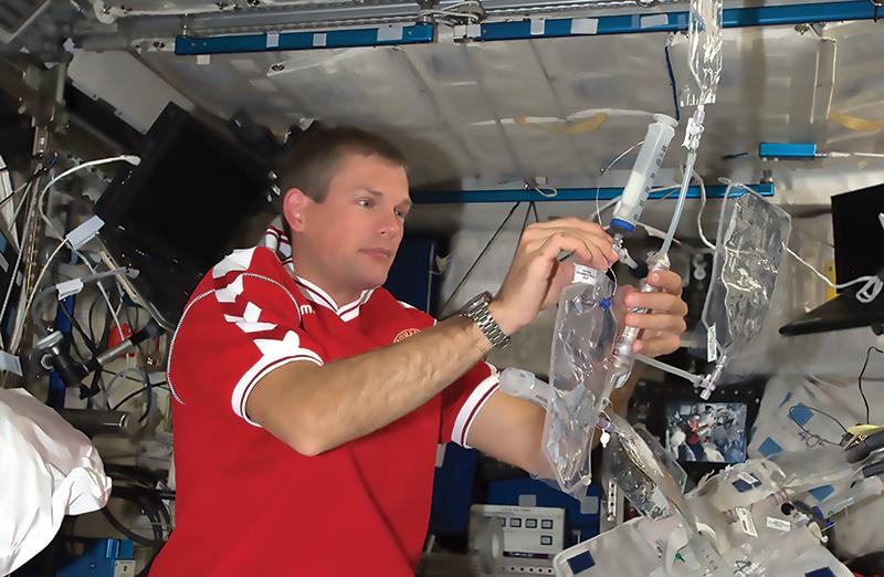 Космонавт на космической станции работает с прототипом системы очистки воды на основе мембран, пропитанных аквапоринами.