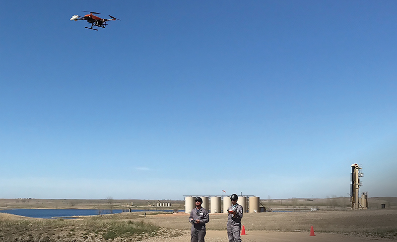 Technicians fly a drone outfitted with SeekOps' methane detector