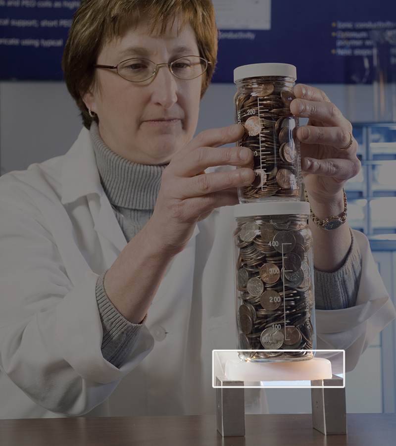 NASA scientist Mary Ann Meador stacks jars of coins on a piece of aerogel