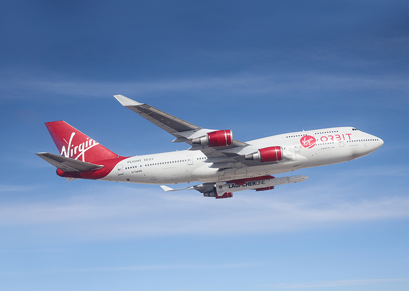 Virgin Orbit's specially equipped Boeing 747 flies in blue skies with small rocket attached underneath