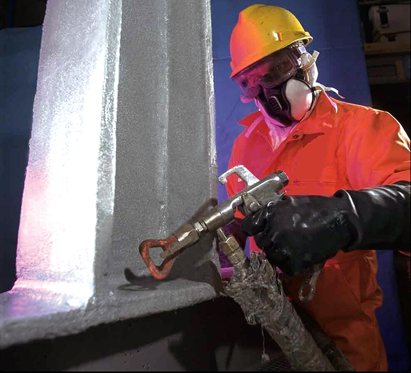 A worker in protective clothing sprays a fire resistant coating onto a steel beam