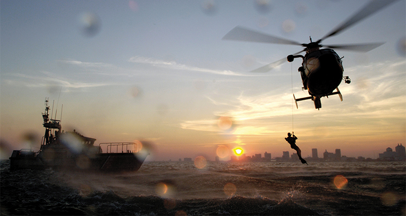 Rescue swimmer lowered by helicopter line to rough waters