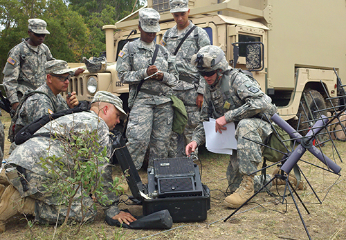 Service members in camouflage dress crowd around field communication equipment