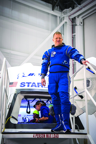 Crew member stands outside the Boeing Starliner spacecraft