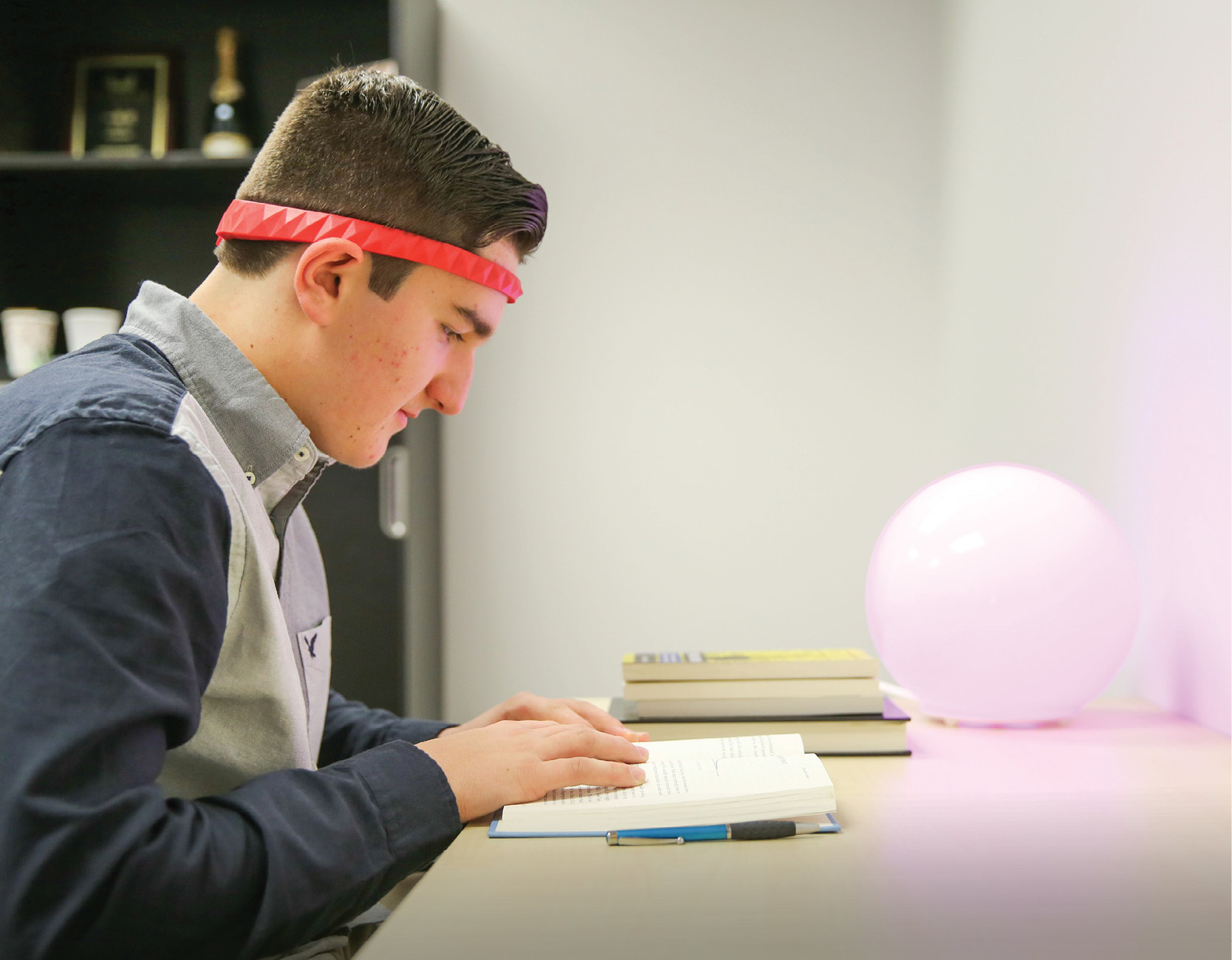 A student reading while wearing BrainCo's LUCY headband