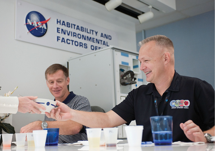 NASA astronauts Doug Hurley takes a bowl at a food tasting even at Johnson Space Center
