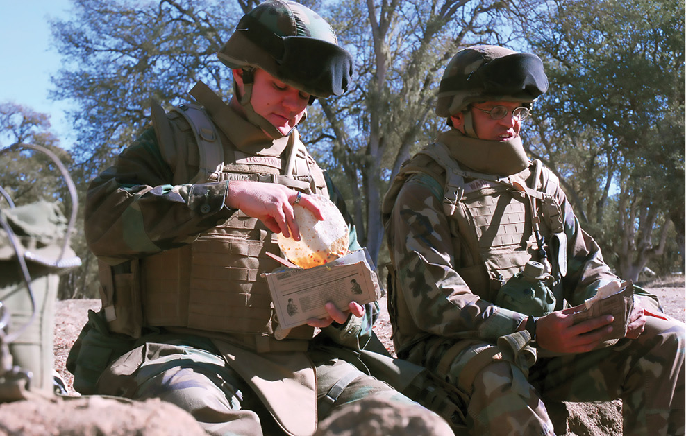 Two soldiers eat a packaged meal