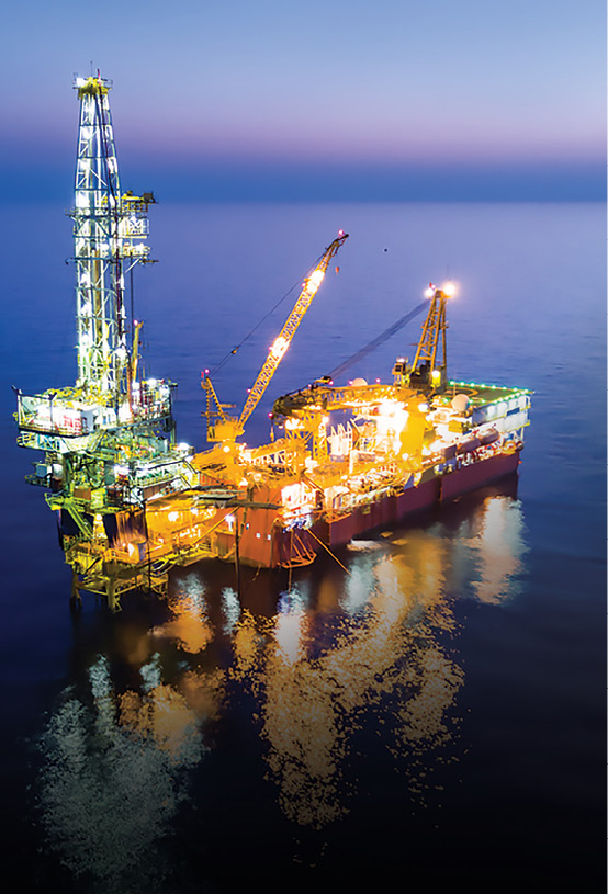 An offshore oil platform is lit up at night