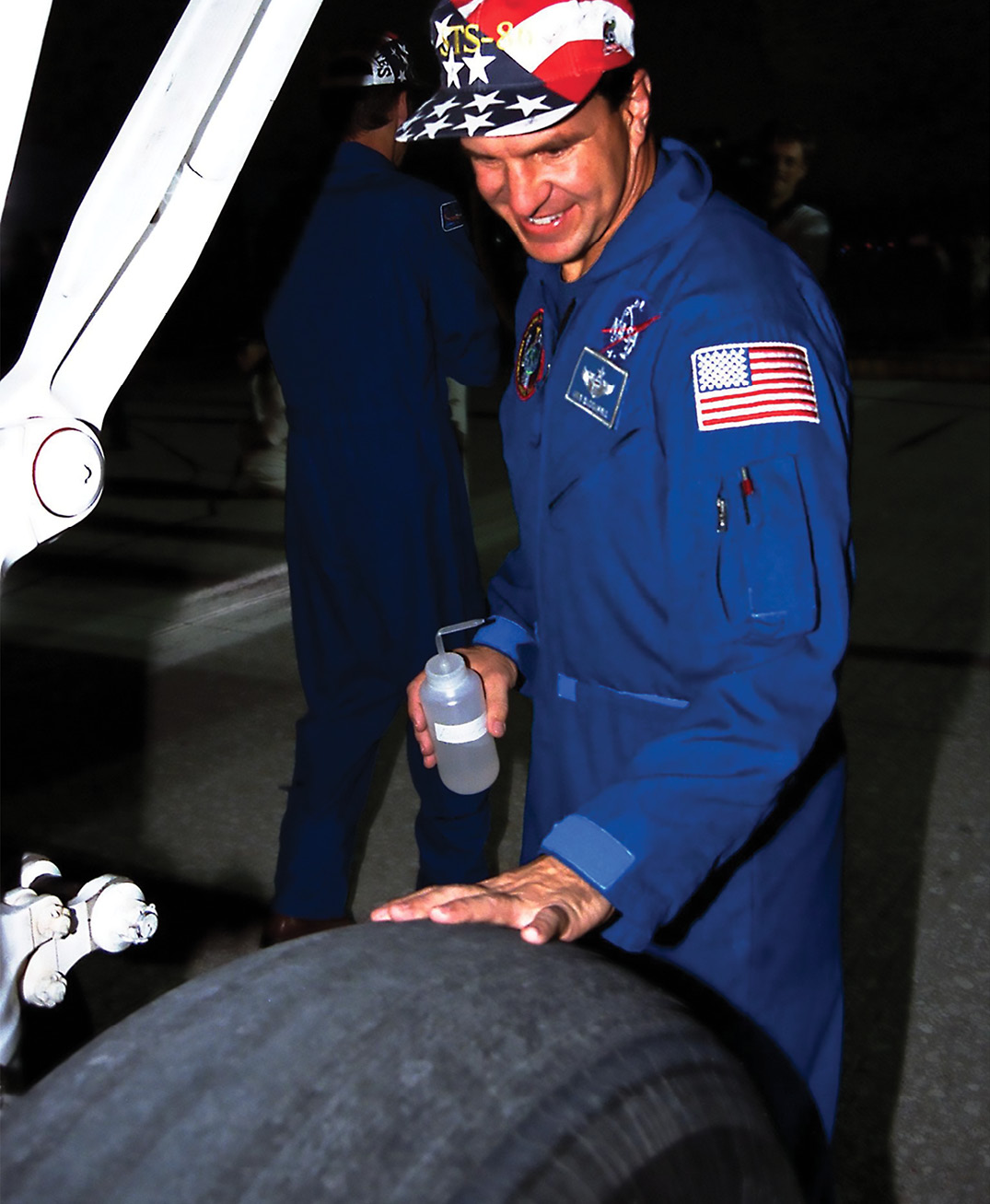 Astronaut Michael Bloomfield inspects a Space Shuttle tire