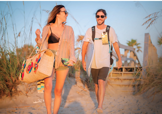 Two beachgoers carrying Phoozy insulated smartphone cases
