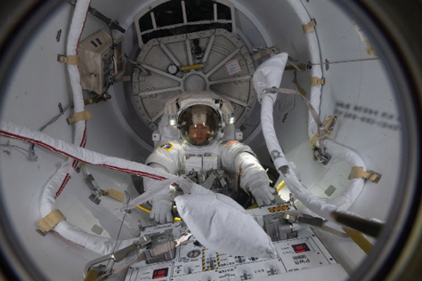 U.S. astronaut Christina Koch in a spacesuit enters an airlock on the space station