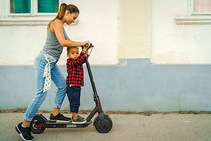 A woman and a child  on an electric scooter