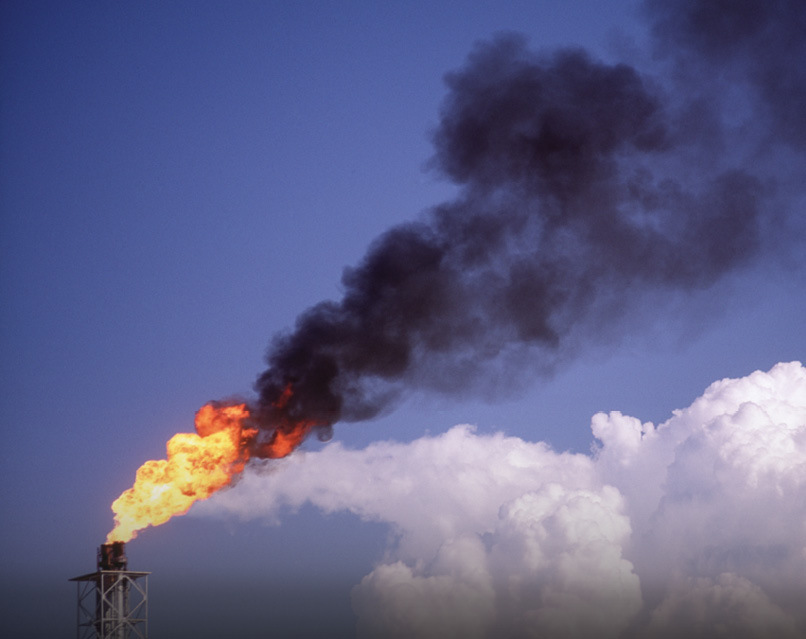 Flames and smoke flare from the top of an oil well into the blue sky