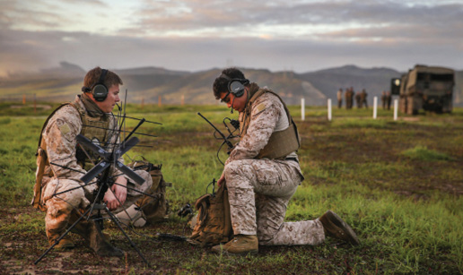 Two male servicemembers set up communications equipment in the field