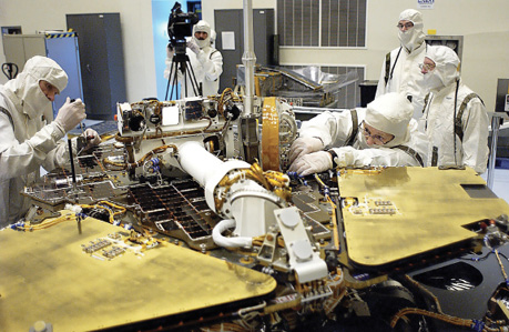 Technicians in clean room gear remove a circuit board from the Mars Exploration Rover 2
