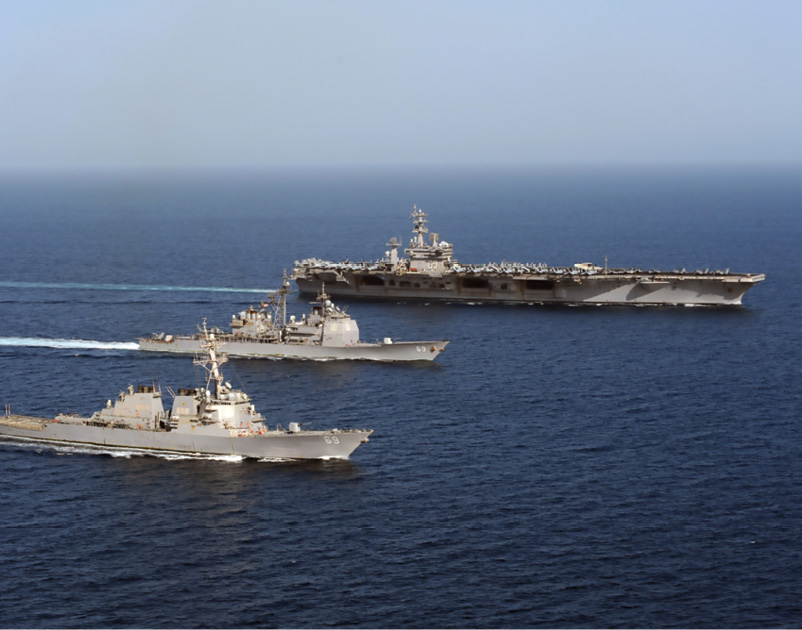 A U.S. Navy aircraft carrier and two more ships navigate in parallel on deep blue water