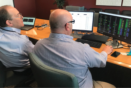Mosaic CEO Chris Brinton and a retired air traffic coordinator look at a computer