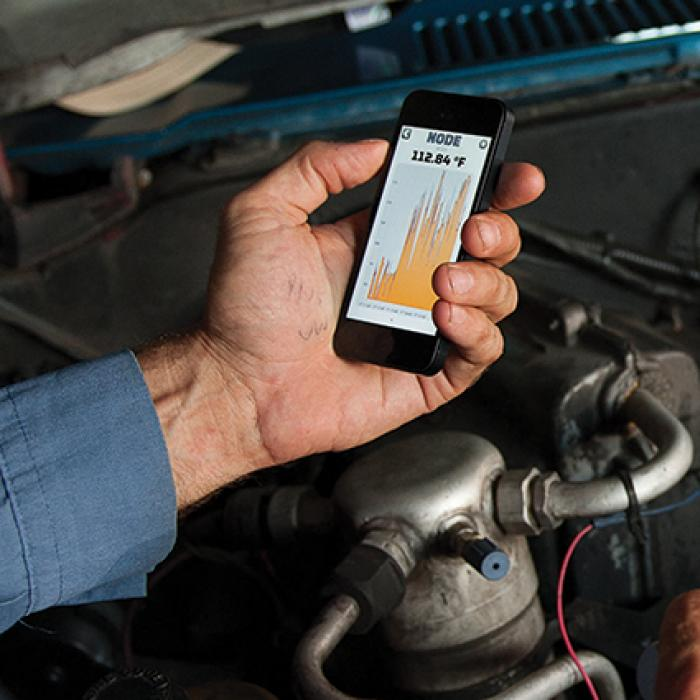 Mechanic using diagnostic tool on car engine