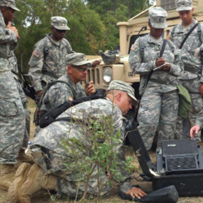 Service members crowd around field communication equipment