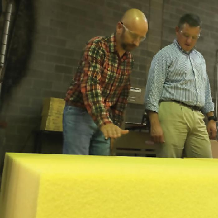 Boyd Corporation manager James Williams and local Congressman Bruce Westerman look at bright yellow Solimide panels