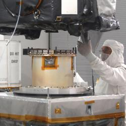 Engineer in clean room gear attaches spacecraft to separation device