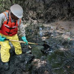 Worker cleaning an oil spill